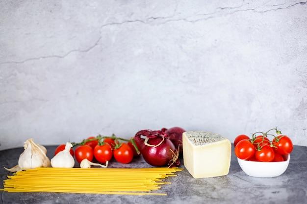Gesunde italienische küche, zutaten für spaghetti, tomaten, kirsche, käse und knoblauch
