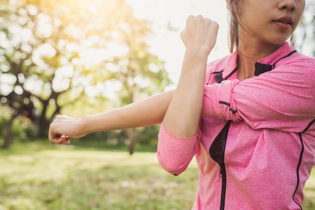 Gesunde junge asiatische frau, die am park trainiert