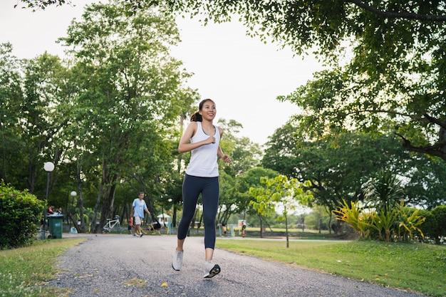 Gesunde junge asiatische läuferfrau in der sportkleidung, die auf bürgersteig läuft und rüttelt