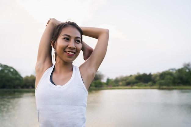 Gesunde junge asiatische läuferfrau wärmen den körper auf, der vor übung und yoga ausdehnt