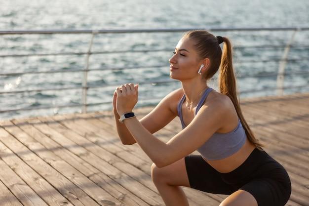 Gesunde junge fitnessfrau, die bei sonnenaufgang am strand kniebeugenübungen macht