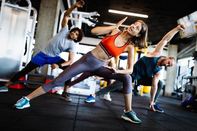 Gesunde junge fitte leute, die übungen im fitnessstudio machen.
