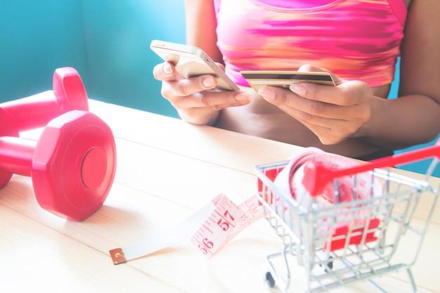 Gesunde junge frau der eignung, die handy verwendet und kreditkarte, onlineeinkaufen hält