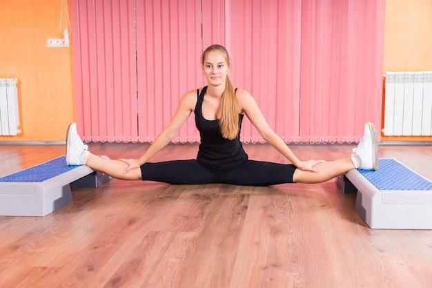 Gesunde junge frau, die ihre beine mit aeroben step-plattformen zu ihren füßen innerhalb der turnhalle ausdehnt.