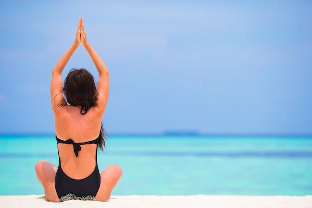 Gesunde junge frau, die in yogaposition meditiert auf dem strand sitzt