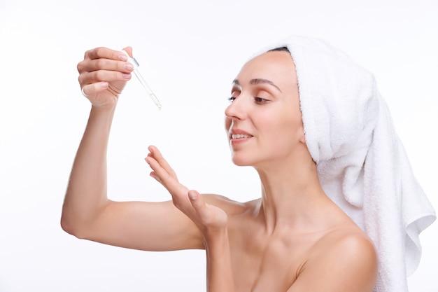 Gesunde junge frau, die revitalisierendes serum von der pipette auf ihrer hand fallen lässt, während sie es nach dem bad auf gesicht und hals aufträgt
