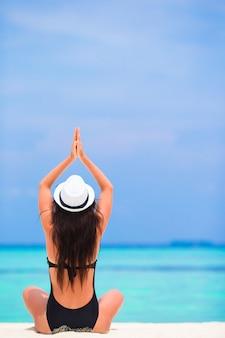 Gesunde junge frau im hut, der in yogaposition meditiert auf weißem sandigem strand sitzt