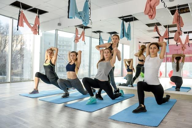 Gesunde, junge gruppe von frauen, die übungen im fitnessstudio machen
