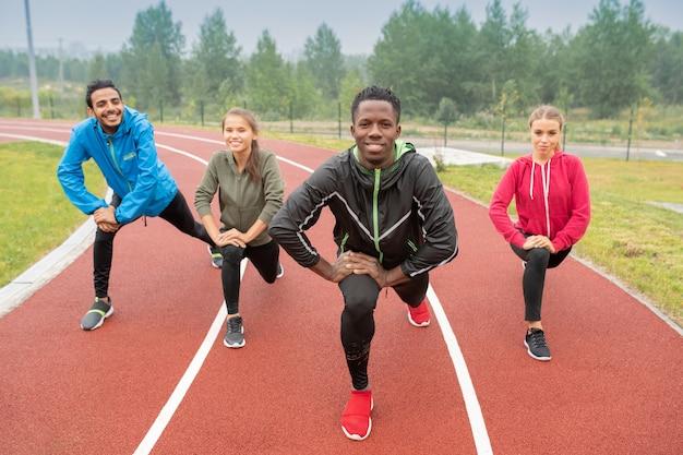 Gesunde junge interkulturelle freunde in aktivkleidung, die während des trainings auf rennstrecken des freiluftstadions trainieren