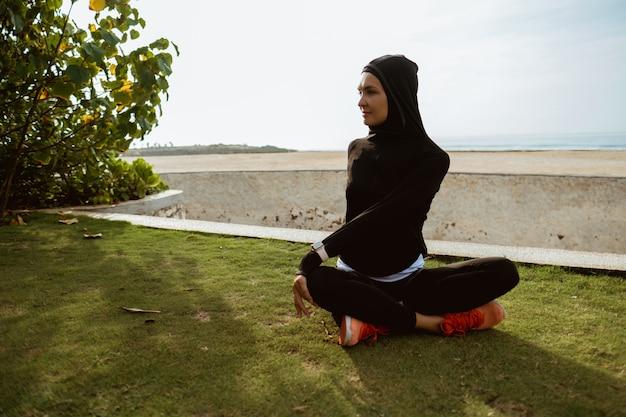 Gesunde junge muslimische frau, die draußen aufwärmt