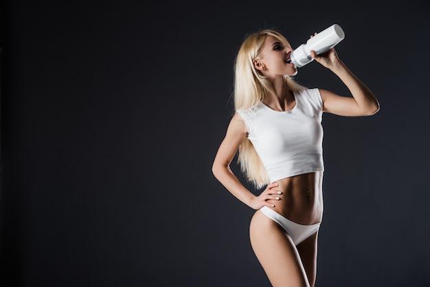 Gesunde junge sexy frau mit perfektem fitnesskörper und gesäßtrinkwasser