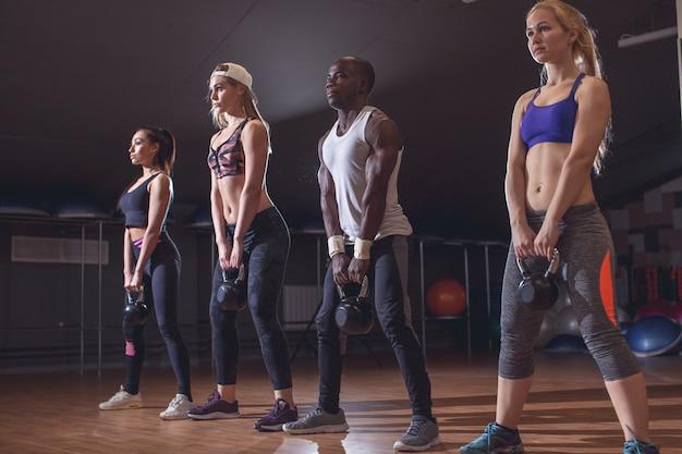 Gesunde junge sportler, die übungen mit kettlebells im fitnessstudio machen
