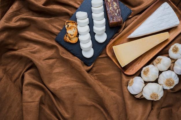 Gesunde käse- und knoblauchknollen angeordnet über zerquetschtem braunem gewebe