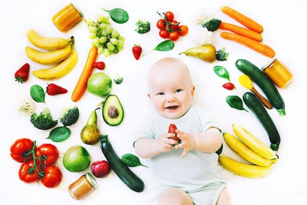 Gesunde kinderernährung lebensmittel hintergrund lächelndes baby 8 monate altbaby erste feste ernährung