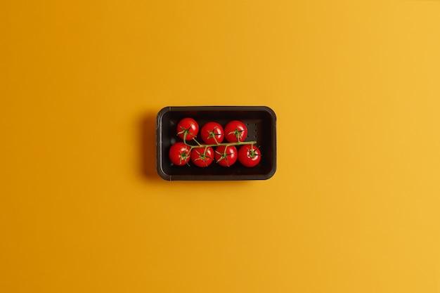 Gesunde kleine kirschtomaten auf einem stiel im schwarzen behälter lokalisiert über gelbem hintergrund. leckeres gemüse für die herstellung von tomatensaft oder vegetarischem sommersalat. perfekte leckere ernte