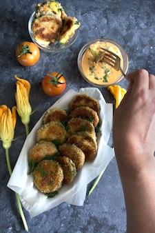 Gesunde kochmahlzeit panierte gebratene zucchini mit tomaten und sauce