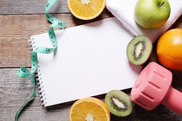 Gesunde komposition mit früchten und notizbuch
