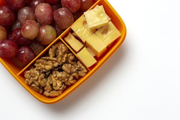 Gesunde lebensmittel in plastikbehältern, die mit käse, trauben und walnüssen auf dem arbeitstisch verzehrfertig sind. zum mitnehmen. walnüsse. isoliert
