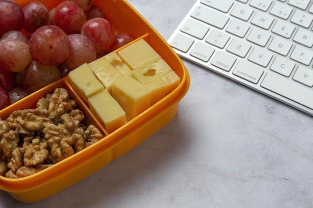 Gesunde lebensmittel in plastikbehältern, die mit käse, trauben und walnüssen auf dem arbeitstisch verzehrfertig sind. zum mitnehmen. walnüsse