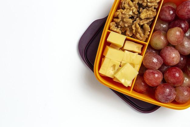 Gesunde lebensmittel in plastikbehältern, die mit käse, trauben und walnüssen auf dem arbeitstisch verzehrfertig sind