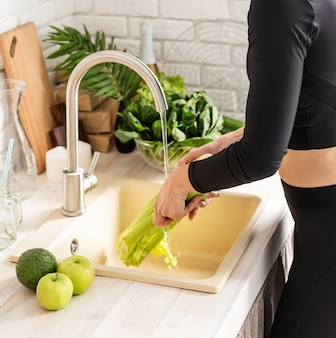 Gesunde lebensmittel zubereiten. junge lächelnde frau in der sportkleidung, die sellerie in der küche wäscht