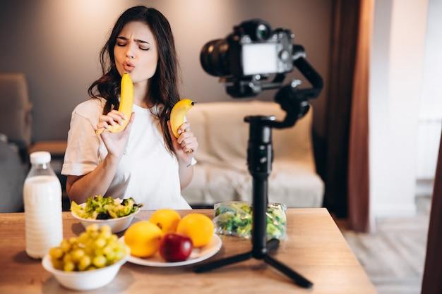 Gesunde lebensmittelblogger junge frau, die frisch von früchten veganen salat im küchenstudio kocht, filmtutorial vor der kamera für videokanal. weibliche influencerin zeigt kein junk food, spricht von gesunder ernährung.