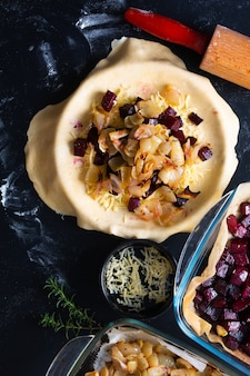 Gesunde lebensmittelkonzeptvorbereitung für selbst gemachte rustikale organische gebratene rote rüben und zwiebelkaramel galette torte