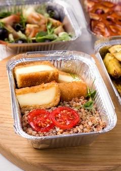 Gesunde lebensmittellieferung. buchweizenbrei in einem behälter mit gemüse und mikrogrün und käse