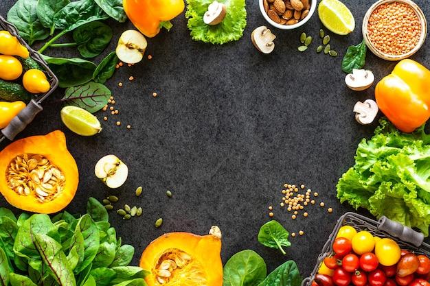 Gesunde lebensmitteloberfläche. herbstfrisches gemüse auf dunkler steinoberfläche mit kopierraum, draufsicht