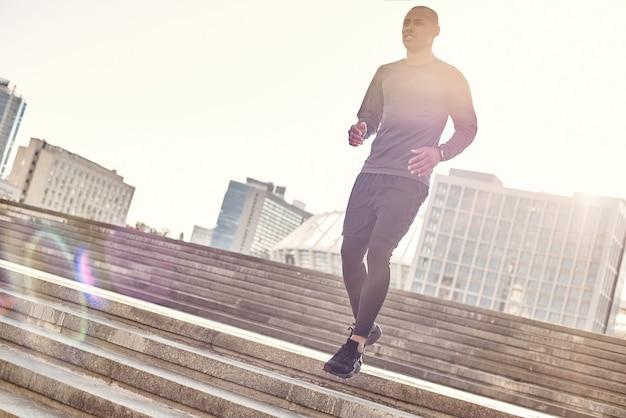 Gesunde lebensweise in voller länge porträt eines athletischen afrikanischen mannes in sportkleidung, die herunterläuft