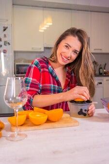 Gesunde lebensweise lebensstil, blonde kaukasische frau, die spaß am frühstück mit frischem orangensaft in ihrer küche hat