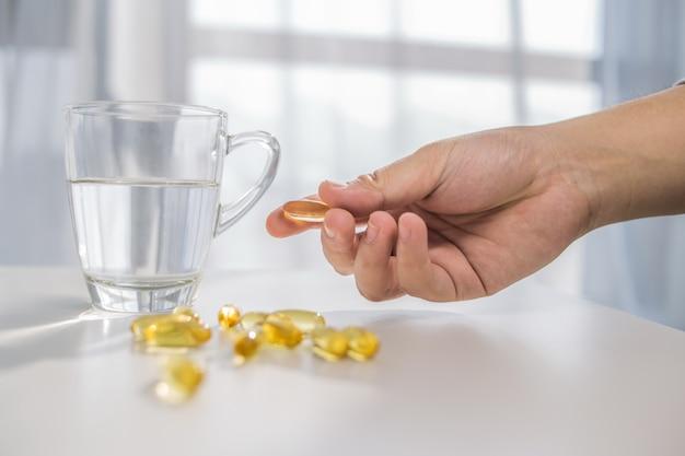 Gesunde lebensweise, medizin, nahrungsergänzungsmittel und menschen konzept - nahaufnahme von männlichen händen halten pillen mit lebertran kapseln und wasser glas