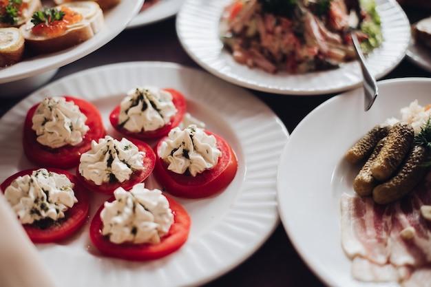 Gesunde leckere snacks auf dem teller. geschnittene tomaten mit frischkäse und kräutern obenauf. weihnachts- oder neujahrsbankett.