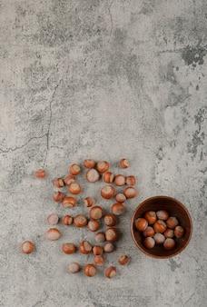 Gesunde macadamia-nüsse in der schale auf einem steinhintergrund.