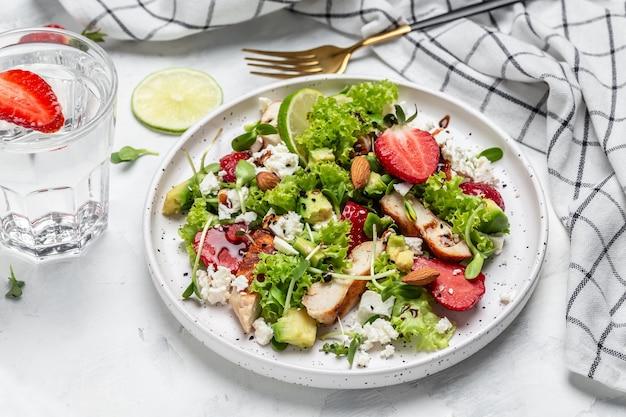 Gesunde mahlzeit erdbeersalat mit hühnerfleisch avocado, feta-käse, salat und nüssen balsamico-essig. detox und gesundes superfoods-konzept.