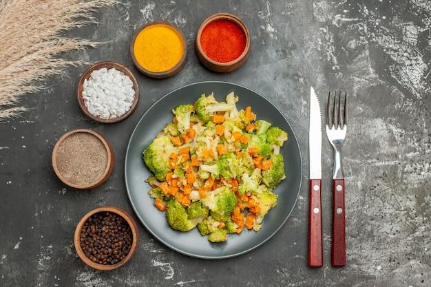 Gesunde mahlzeit mit brokkoli und karotten auf einem schwarzen teller und gewürzen auf grauem tischmaterial