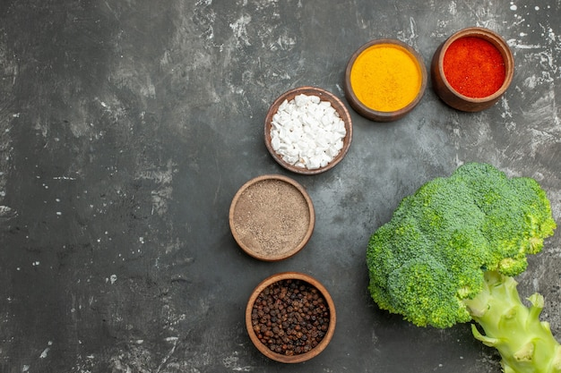 Gesunde mahlzeit mit brokkoli und karotten auf einem schwarzen teller und gewürzen