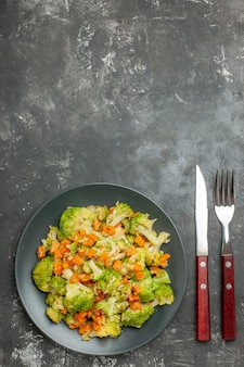 Gesunde mahlzeit mit brokkoli und karotten auf einem teller mit gabel und messer auf grauem tisch