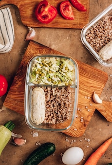 Gesunde mahlzeitenzubereitungsbehälter mit hausgemachten hühnerwürsten, buchweizen und gemüsesalat auf rustikalem hintergrund. diät, gewichtsverlustkonzept. ansicht von oben. flach legen