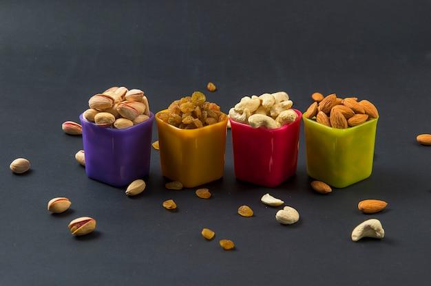 Gesunde mischung trockenfrüchte und nüsse auf dunklem hintergrund. mandeln, pistazien, cashewnüsse, rosinen