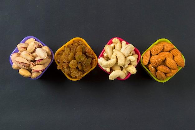 Gesunde mischung trockenfrüchte und nüsse im dunkeln. mandeln, pistazien, cashewnüsse, rosinen