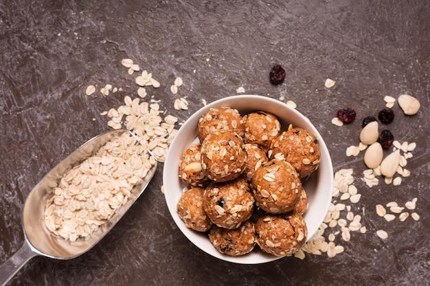 Gesunde müslikapseln aus bio-energie mit nüssen, kakao, hafer und rosinen - vegetarische süße bissen ohne zucker. dunkler hintergrund, draufsicht