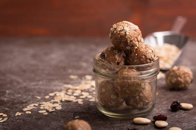 Gesunde müslikapseln aus bio-energie mit nüssen, kakao, hafer und rosinen - vegetarische süße bissen ohne zucker. dunkler hintergrund