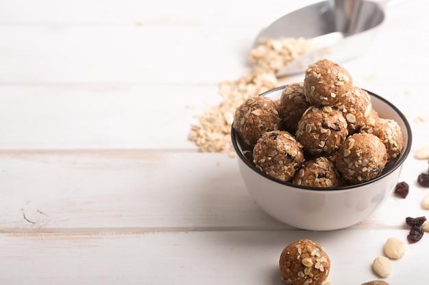 Gesunde müslikapseln aus bio-energie mit nüssen, kakao, hafer und rosinen - vegetarische süße bissen ohne zucker. kopieren sie platz für text