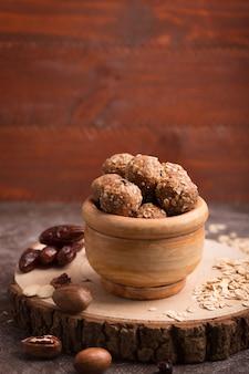Gesunde müslikapseln aus bio-energie mit nüssen, kakao, hafer und rosinen - vegetarische süße bissen ohne zucker. vertikale ausrichtung mit kopierraum