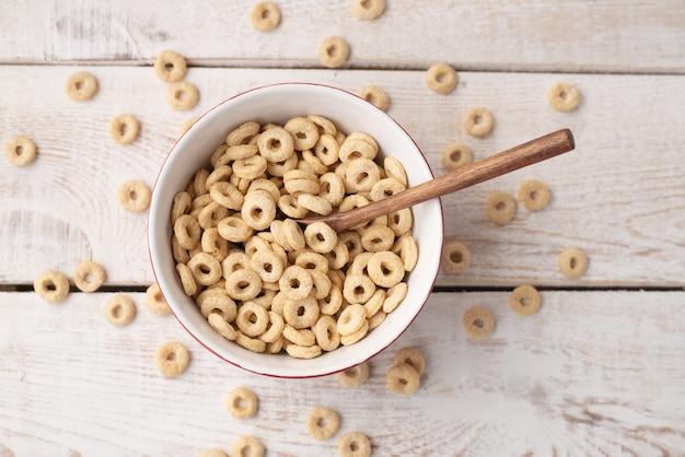 Gesunde müsliringe auf hellem holzhintergrund in einem teller und verstreut auf dem tisch. trockenes müsli.