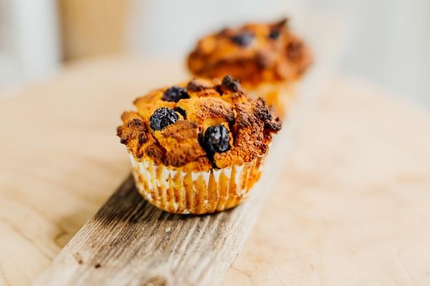 Gesunde muffins mit kokosmehl und blaubeeren auf hellem holzteller dekoriert mit minze und conc