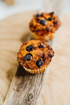 Gesunde muffins mit kokosmehl und blaubeeren auf hellem holzteller dekoriert mit minze