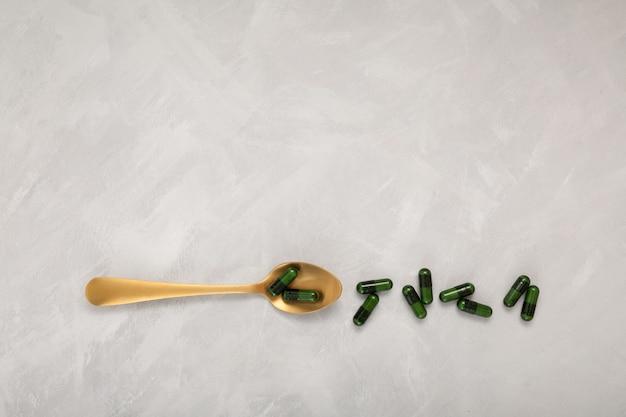 Gesunde nahrungsergänzungsmittel in grünen kapseln pillen in goldenem löffel alternativmedizinkonzept