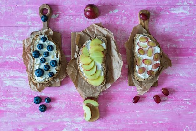 Gesunde offene sandwiche mit früchten, pfirsichtraubenblaubeeren und weichkäse auf rosa hölzernem hintergrund, draufsicht, ebenenlage